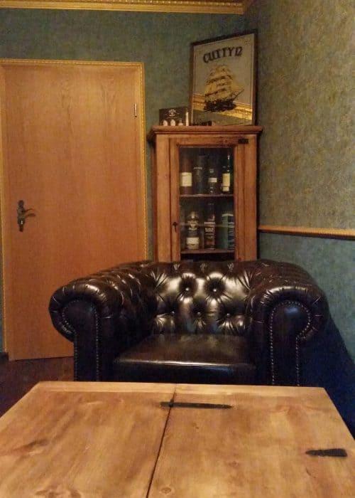 Blick auf den Chesterfield Sessel und die Whisky Vitrine